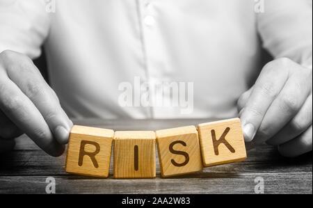 El hombre descuidadamente plantea la palabra riesgo. La prudencia y previsión de posibles problemas y perturbaciones. Planificación y estrategia de acción. Analytics. Alto riesgo
