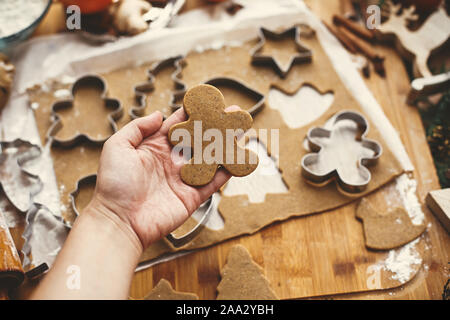 Hacer galletas de jengibre de navidad. Mano sujetando las materias gingerbread man cookie en el fondo de la masa, cortadores de metal y el anís, el jengibre, la canela, el pino