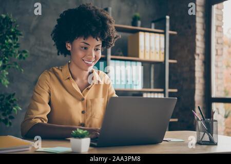 Foto de alegre positivo raza mixta chica sonriente toothily trabajando en la presentación sobre su corporation usando en el escritorio portátil