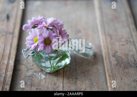 Purple Asters en un pequeño vaso de vidrio desde arriba en un desvencijado rústico con muebles de madera
