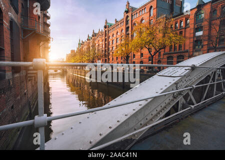 Puente en arco a través de canales en la Speicherstadt de Hamburgo, Alemania, Europa. Histórico edificio de ladrillo rojo iluminado por la luz del atardecer dorado suave caliente.
