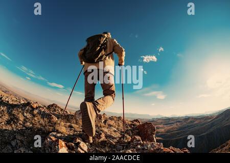 Caminante el hombre entra en la zona de las montañas al atardecer el tiempo
