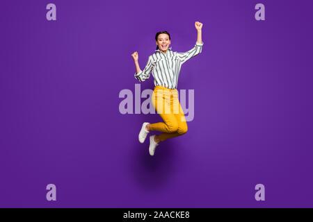 Sí. Foto de longitud completa de crazy bella dama saltando alto celebrando la victoria levantando los puños del deporte llevan camisa a rayas amarillas aislado pantalones