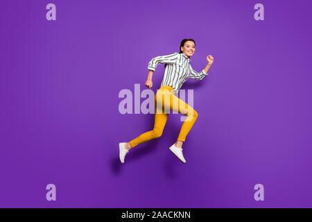Foto de perfil de longitud completa de locura hermosa dama saltando alto corriendo precios de descuento compras camisa a rayas de desgaste pantalón amarillo morado aislado