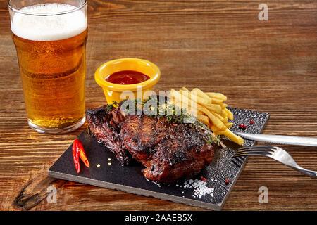 Vaso de cerveza con filete gourmet y patatas fritas en el fondo de madera.