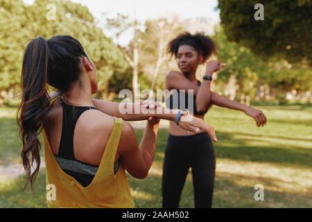 Dos jóvenes de gimnasia deportiva femenina diversos amigos de estirar sus músculos en el parque en un día de verano - dos amigos que trabajan juntos