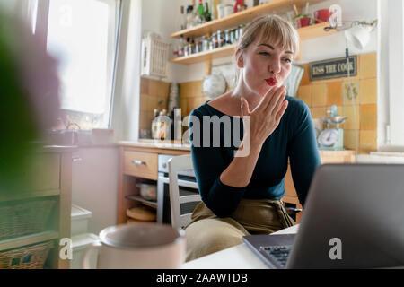 Retrato de mujer joven con el portátil en la cocina, soplando un beso