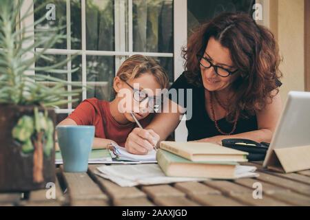 Cansado estudiante haciendo los deberes en casa con libros de texto, periódicos y pad digital ayudado por su madre. Mum escrito sobre el copybook enseñar a su hijo.