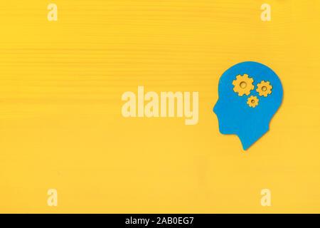 Cerebro trabaja de concepto. Las ideas, la creatividad concepto de la cabeza humana con engranajes sobre fondo amarillo