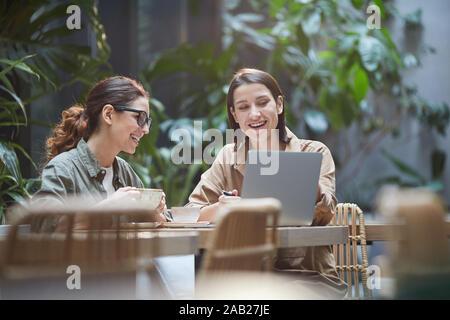 Retrato de dos jóvenes mujeres reír alegremente mientras se utiliza el portátil en un café en la terraza al aire libre decorado con plantas, espacio de copia