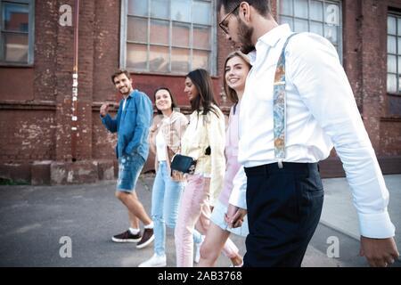 Grupo de jóvenes amigos felices divirtiéndose en las calles de la ciudad