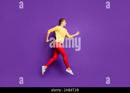 Foto de perfil de longitud completa de gracioso dama milenario saltando de alta velocidad comercial venta prisa vestirse con chaqueta amarilla pantalón rojos aislados