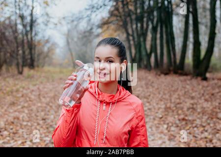 Joven Mujer hermosa agua potable durante la mañana jogging en el parque de otoño
