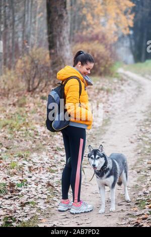 La mujer va con un perro a caminar en el parque en otoño
