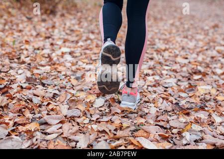 Cerca de los pies de un corredor corriendo en hojas de otoño en el parque