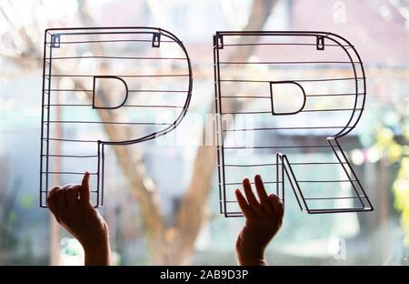 Cartas de relaciones públicas frente a la ventana. Mantenga las manos de metal 3d letras de retroiluminación. Marketing y Negocios de la concepción.