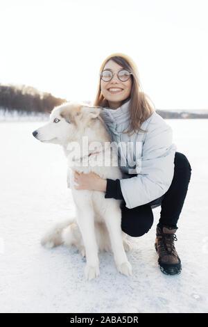 Niña feliz jugando con perros husky siberiano en Winter Park. Caminan sobre un lago congelado