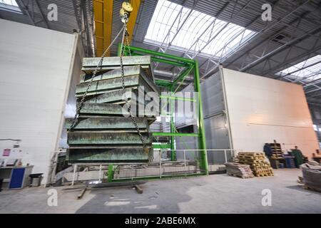 Grúa industrial lleva encofrados para losas de hormigón. Planta de hormigón. Los trabajadores de los talleres de la planta de construcción de viviendas. Interior Industrial.