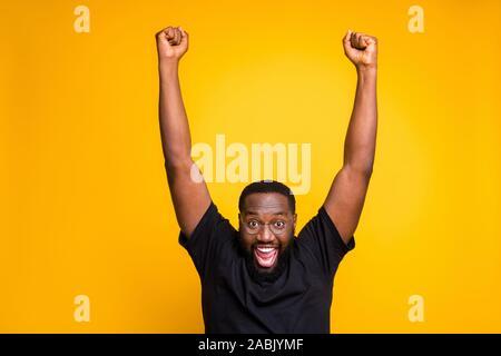Foto de emocionada alegría regocijo hombre expresar emociones locas en la cara en gafas elevando sus puños arriba tras ganar boletos para ir al extranjero en