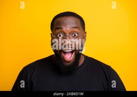 Cerrar Foto de extático regocijo hombre regocijarse en las ventas comenzaron con entusiasmo en la cara gritando con las gafas en t-shirt aisladas de color vibrante