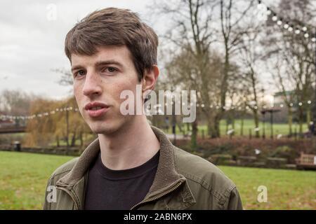 Cerca de la cabeza y los hombros de un joven en su adolescencia o principios del veinte caminando en un parque.