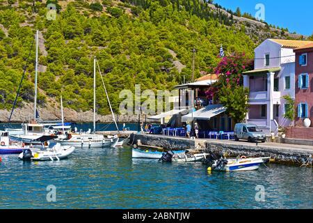 Bonitas vistas sobre el puerto natural de la aldea de beautifulcoastal Assos. Embarcaciones de recreo amarradas en frente de harborside restaurant cafés.