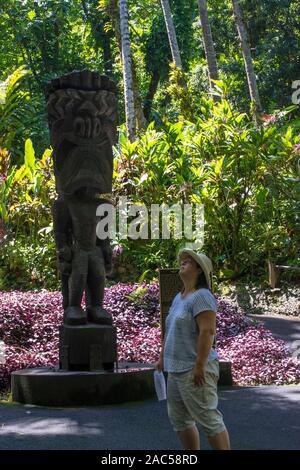 Una mujer mira hasta cerca de un tiki tallada en madera del dios hawaiano 'Ku' en el jardín botánico tropical de Hawaii, Papa'ikou, Isla Grande de Hawaiʻi.