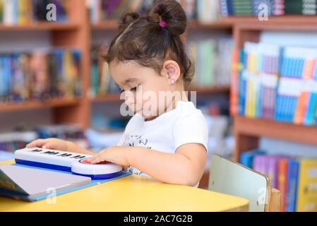 Niño pequeño adentro delante de los libros. Cute Niño Pequeño sentado en una silla cerca de la Mesa y jugar con el piano de juguete. Cabrito en una librería, rodeado de coloridos libros. Feliz chica multirace tocar el piano.
