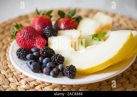 Melón cortado y bayas. Ensalada de frutas de fresas, arándanos, melón, menta y moras. Dieta ensalada en la placa blanca - desayuno, pérdida de peso.