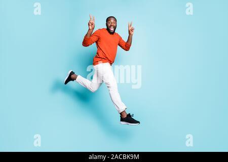Cuerpo de longitud completa tamaño foto de alegre hombre casual positivo ejecutando saltando mestizos vistiendo pantalones pantalones blancos sneakers mostrando signo v doble