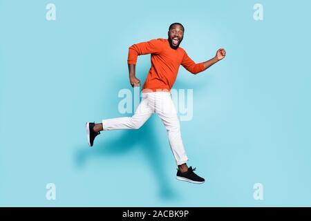 Fotografía tamaño corporal de longitud completa el perfil lateral del hombre de raza mixta expresando emociones positivas usar zapatillas pantalones blancos pantalones ejecutando saltando