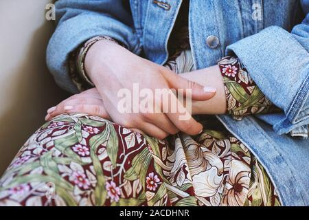 Sección intermedia de joven mujer vistiendo chaqueta de dril de algodón durante el verano vestido con patrón floral - Cierre de manos femeninas doblada en su regazo