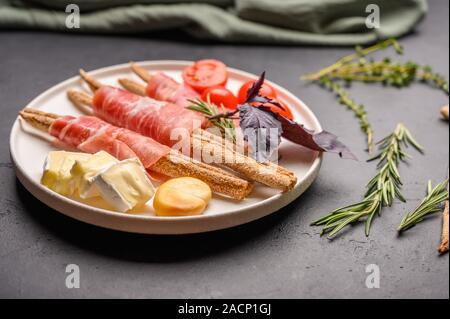 Comida italiana tradicional es grissini pan con jamón, queso y tomates con hierbas en un plato sobre un fondo oscuro. Cerrar