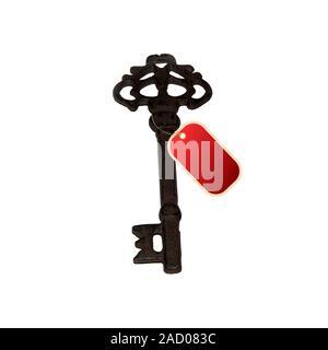 Antique vintage clave. Etiqueta roja en blanco colgando de la llave sobre un fondo blanco. Stock Image Foto de stock