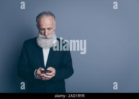 Retrato de su él agradable atractivo chic classy centró concentrado hombre canoso vistiendo, tux usando dispositivo moderno gadget escribiendo mensajes sms aislar