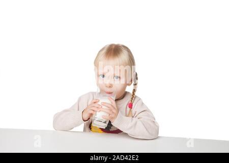 Retrato de una bonita niña beber leche, aislado en blanco