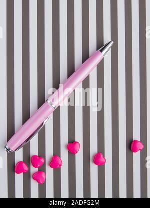 El trabajo creativo de una mujer diseñador, sobre un fondo de rayas blanco-negro se encuentra una pluma rosa y pequeñas gotas en forma de corazones, Flatlay vista superior