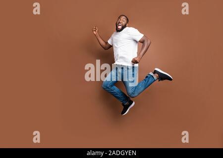 Cuerpo de longitud completa tamaño foto de urgente saltar corriendo gritando guy aspira a terminar persiguiendo sus objetivos con jeans denim camiseta blanca aislada