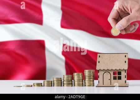 Hombre sujetando monedas poniendo en casa de madera hucha, Dinamarca ondear la bandera en el fondo. Ahorro de dinero para la hipoteca.