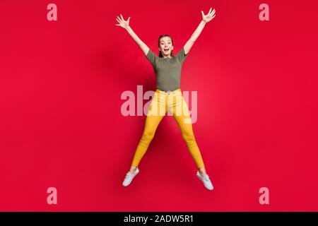 Foto de longitud completa loco dama milenario saltar un elevado gasto en tiempo libre humor alegre excitado vestirse con unos pantalones amarillos camiseta verde aislado
