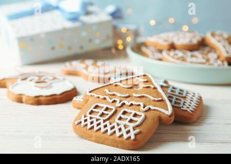 Placa con galletas de Navidad caseras, cajas de regalo sobre la mesa de madera blanca, contra el fondo azul. Closeup