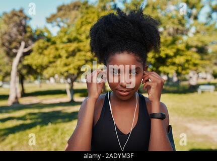 Retrato de una mujer africana que confía el corredor estadounidense atleta escucha música con los auriculares en el parque Foto de stock