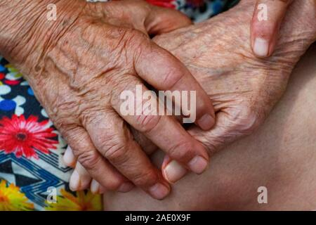 Ancianos, marido y mujer se dan la mano con amor. Los abuelos mantenga las manos de cada uno. Los jubilados en un hogar de ancianos se aburre.