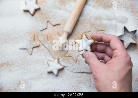 Cerca del hombre mano sosteniendo estrella contra la cookie cutters, masa, rodillo y galletas en el fondo.