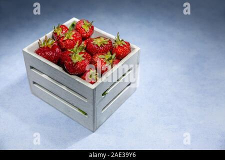 Las fresas, fruta típica del verano colocarlos en una pequeña caja de madera sobre un fondo de textura de color pastel. Una buena y saludable el tipo de fruta que contiene pocos