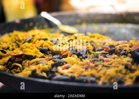 Una olla grande de recién cocinado una paella con arroz con azafrán, marisco y mejillones en un ángulo bajo vista con el enfoque selectivo y copie el espacio en un concepto de catering Foto de stock
