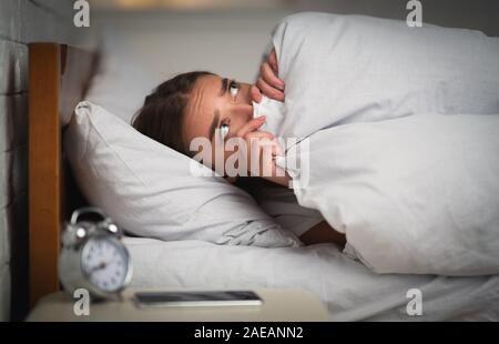 Asustada chica acostado en la cama incapaz de dormir