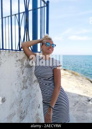 Feliz joven mujer rubia en traje a rayas marinas posando en el mar Mediterráneo