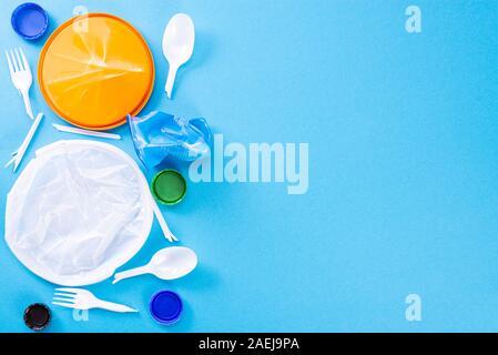 Los residuos domésticos en un fondo azul. El concepto de clasificación de polietileno, plástico, cartón, papel, vidrio. La protección del medio ambiente, ecología