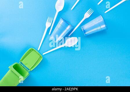 Los residuos domésticos en un fondo azul y un contenedor de basura. El concepto de clasificación de polietileno, plástico, cartón, papel, vidrio. Ambientales
